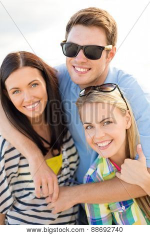 summer holidays, vacation, tourism, travel and people concept - group of happy friends hugging over sky background
