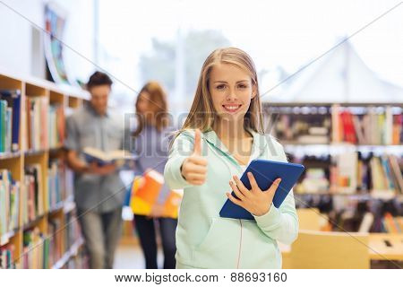 people, education, technology, gesture and school concept - happy student girl or woman with tablet pc computer showing thumbs up in library
