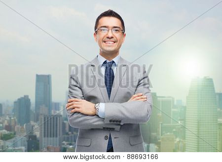 business, people and vision concept - happy smiling businessman in eyeglasses and suit over city background