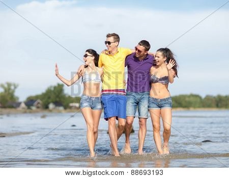 summer holidays, vacation, tourism, travel and people concept - group of happy friends walking and waving hands along beach