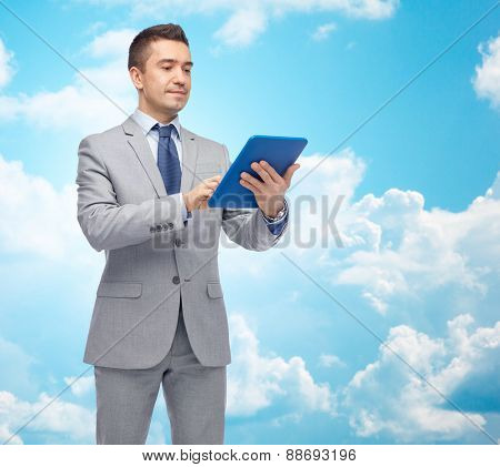 business, people and technology concept - happy businessman in suit holding tablet pc computer over blue sky with clouds background