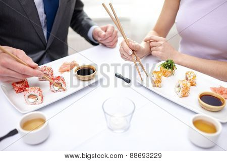 restaurant, food, people, date and holiday concept - close up of couple eating sushi at restaurant