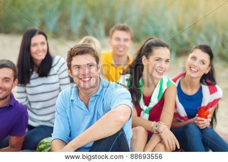 summer holidays, vacation, tourism, travel and people concept - group of happy friends sitting on beach