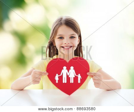 childhood, love, charity, ecology and people concept - smiling little girl sitting and holding red heart cutout over green background