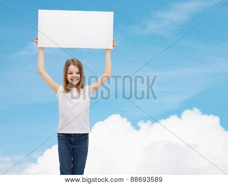advertisement, childhood, happiness and people concept - smiling little child in white t-shirt holding blank board over blue sky with cloud background