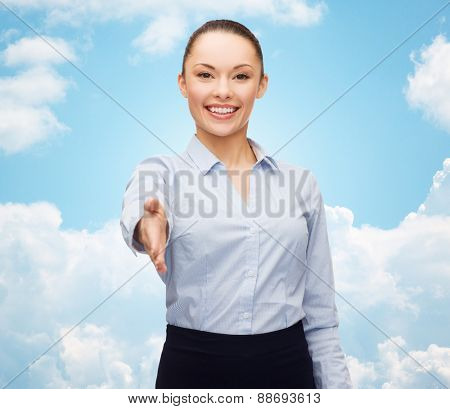 business, gesture and education concept - friendly young smiling businesswoman with opened hand ready for handshake dollar,