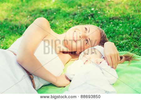 family, child and parenthood concept - happy mother lying with little baby on blanket in park