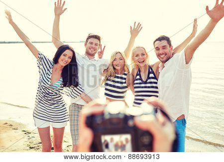 summer, sea, tourism, technology and people concept - group of smiling friends with camera on beach waving hands and photographing