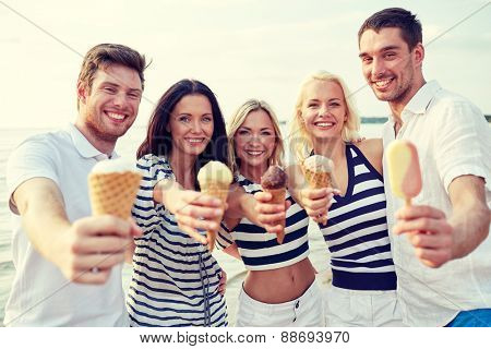 summer, holidays, sea, tourism and people concept - group of smiling friends showing ice cream on beach