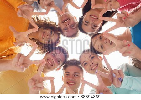 friendship, youth, gesture and people - group of smiling teenagers in circle showing victory sign