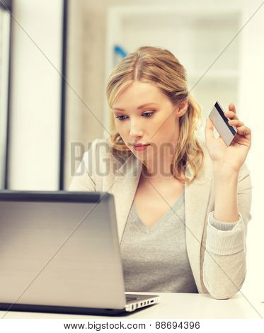 picture of serious woman with laptop computer and credit card.