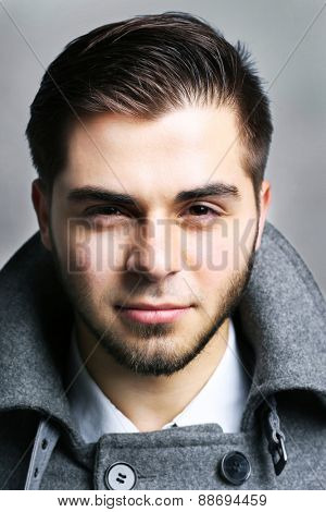 Young man in coat on gray background