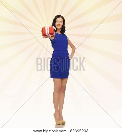people, holidays, greetings, gifts and shopping concept - happy young woman in blue dress with present over beige burst rays background