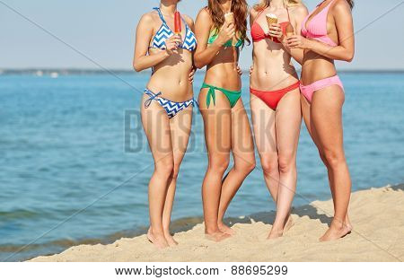 summer vacation, holidays, party, travel and people concept - close up of young women with ice cream on beach