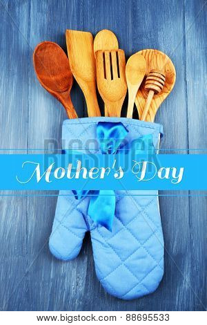 Different kitchen utensils in potholder on wooden background, Mother's Day greeting card