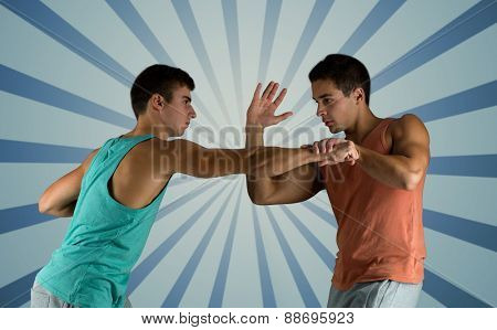 sport, competition, strength and people concept - young men fighting hand-to-hand over blue burst rays background