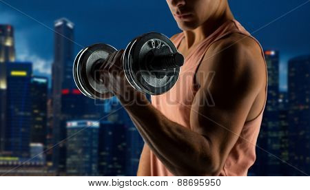 sport, fitness, weightlifting, bodybuilding and people concept - close up of young man with dumbbell flexing biceps over night city background