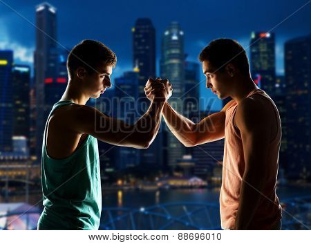 sport, competition, strength and people concept - two young men arm wrestling over night city background