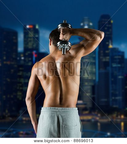 sport, fitness, weightlifting, bodybuilding and people concept - young man with dumbbell flexing biceps over night city background from back