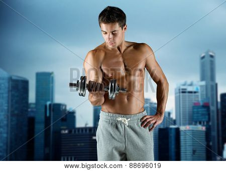 sport, fitness, weightlifting, bodybuilding and people concept - young man with dumbbell flexing biceps over night city background