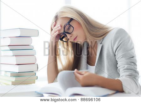 student with pile of books and notes studying indoors