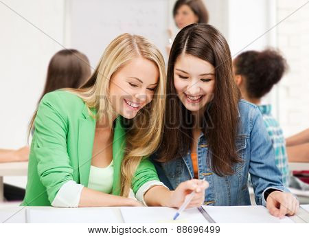 education concept - student girls pointing at notebook at school