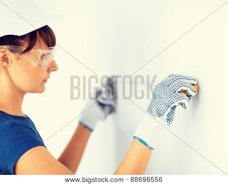 architecture and home renovation concept - female architect measuring wall with flexible ruller