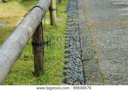 Short Bamboo Fence And Stones Along Path