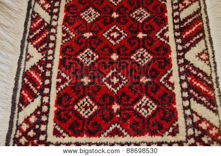 Small wool rug with red background