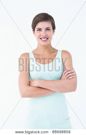 Happy brunette looking at camera with arms crossed on white background