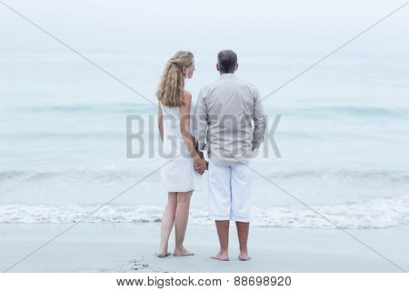 Happy couple standing by the sea and holding hands at the beach
