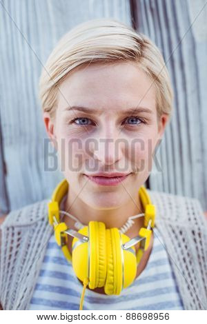 Pretty blonde woman wearing yellow headset on wooden background