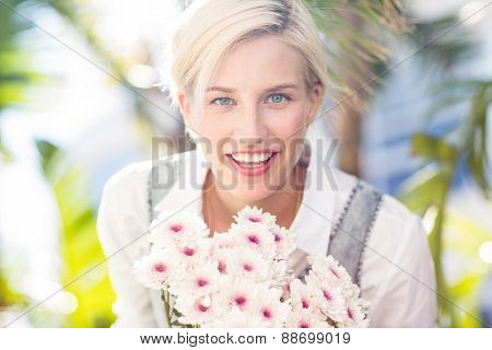 Pretty blonde woman holding bunch of flowers in the park