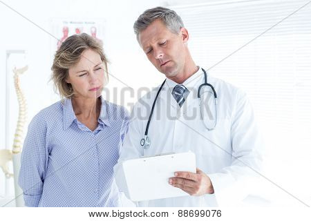 Doctor showing his notes to his patient in medical office