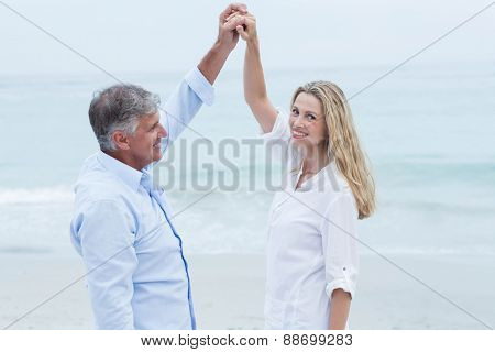 Happy couple dancing by the sea at the beach