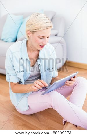 Pretty blonde woman using her tablet on the floor in the living room
