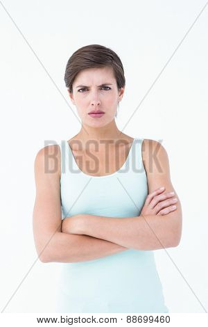 Angry woman looking at camera with arms crossed on white background