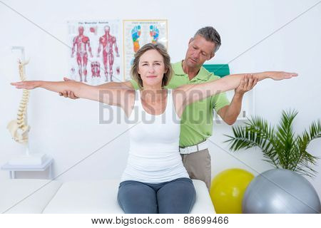 Doctor stretching his patients arms in medical office