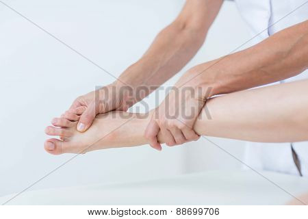 Physiotherapist doing foot massage in medical office