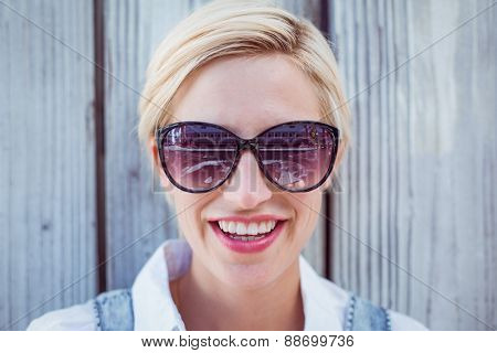 Pretty blonde woman wearing sun glasses on wooden background