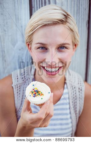 Pretty blonde woman holding cupcake on wooden background