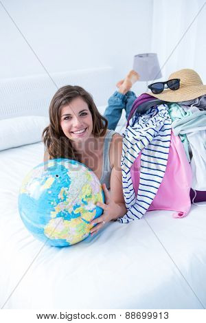 Smiling brunette lying on bed holding her globe at home in the bedroom