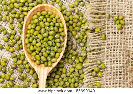 Heap of organic raw green mung bean lentils in wooden spoon