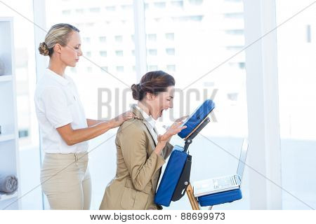 Businesswoman having back massage while using her laptop in medical office
