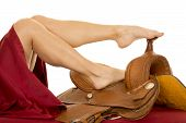 picture of western saddle  - a woman with her legs on top of a saddle - JPG
