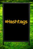 picture of hashtag  - HASHTAGS message on sidewalk blackboard sign against green grass background - JPG