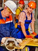 image of millwright  - Happy group people  builder with circular saw - JPG