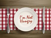 stock photo of anorexic  - top view of I am not hungry written by ketchup on a plate over wooden table - JPG