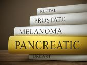 picture of rectal  - book title of pancreatic isolated on a wooden table over dark background - JPG