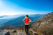 pic of vest  - Sport woman in red vest standing on the top of mountain - JPG